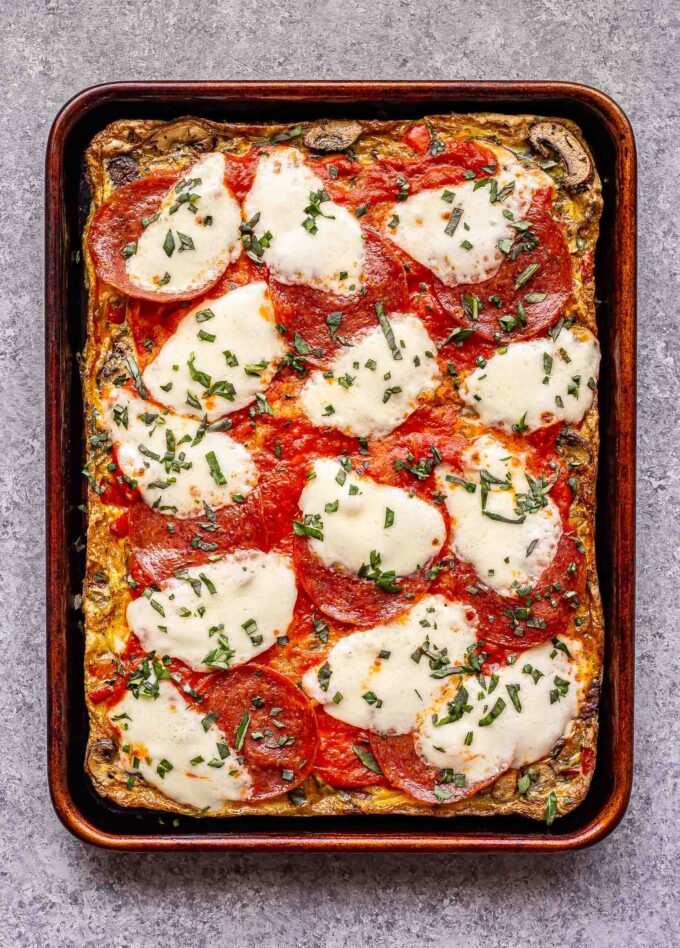 sheet pan pizza frittata topped with marinara sauce, pepperoni and mozzarella cheese.