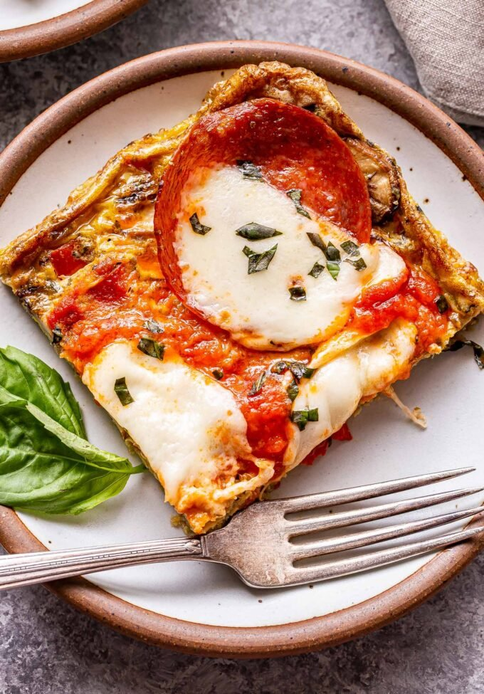 A square slice of pizza frittata on a white plate with a fork.