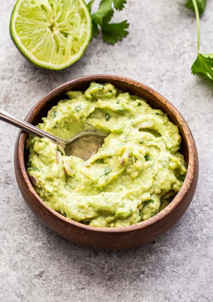 A small wooden bowl with a spoon in it filled with guacamole.