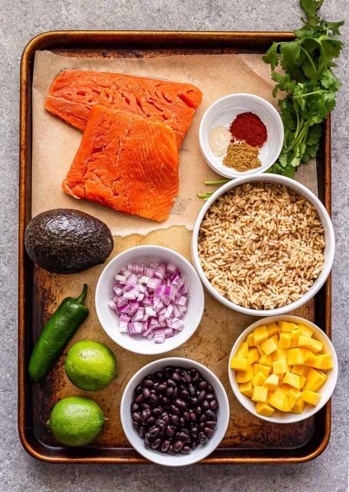 Ingredients used to make Southwest Salmon Rice Bowls on a sheet pan.