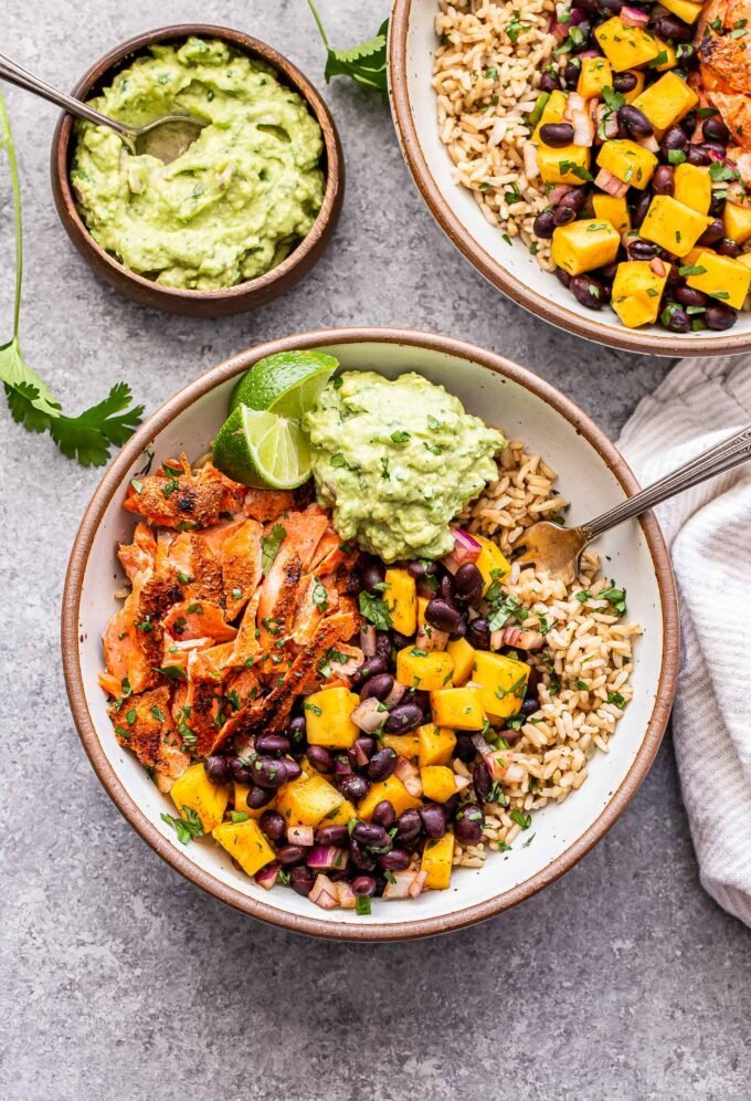 Southwest Salmon Rice Bowls with mango black bean salsa and guacamole in white bowls with a wooden bowl of guacamole next to them.