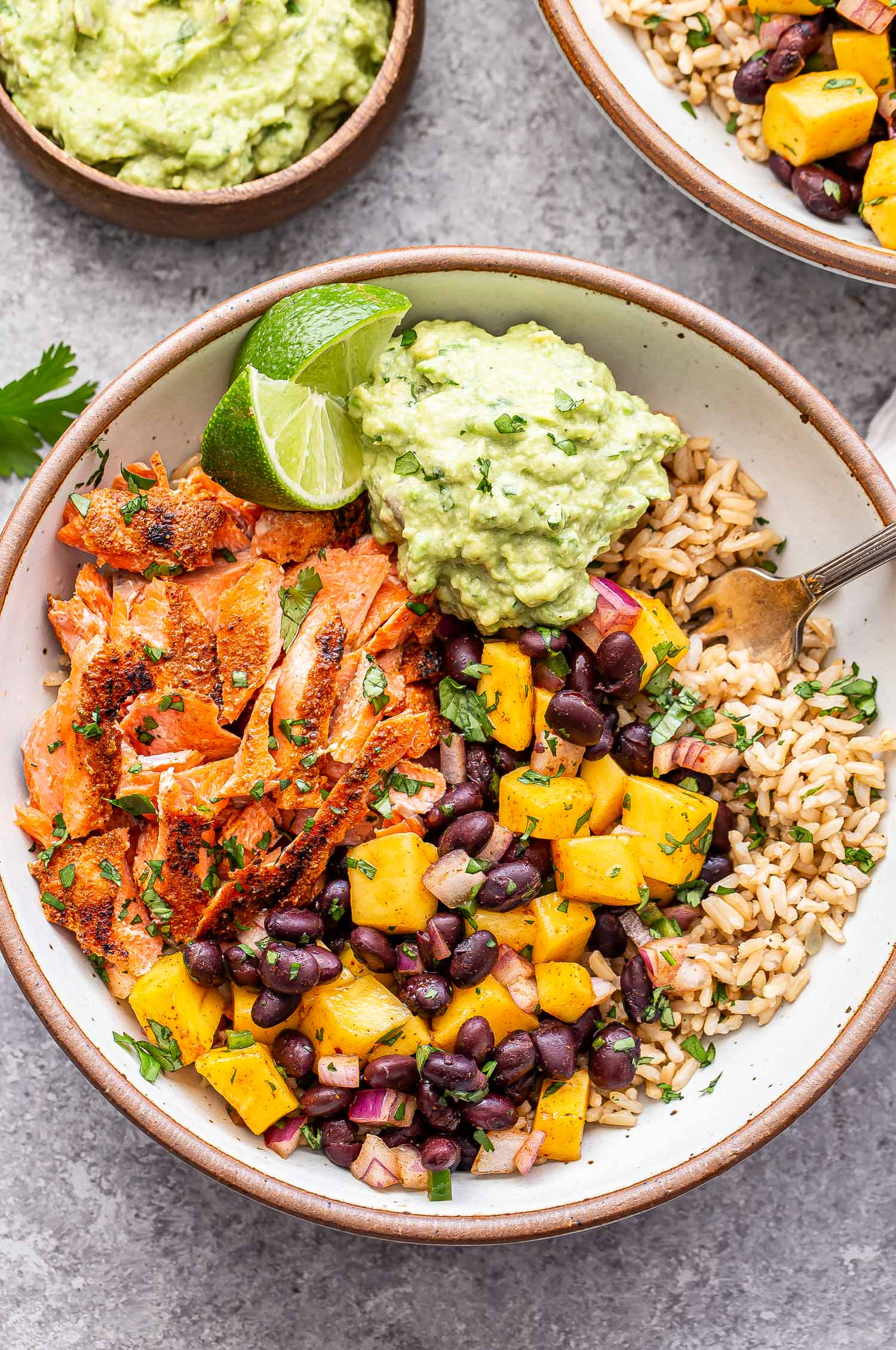 Southwest Salmon Rice Bowls with mango black bean salsa and guacamole in a white bowl.
