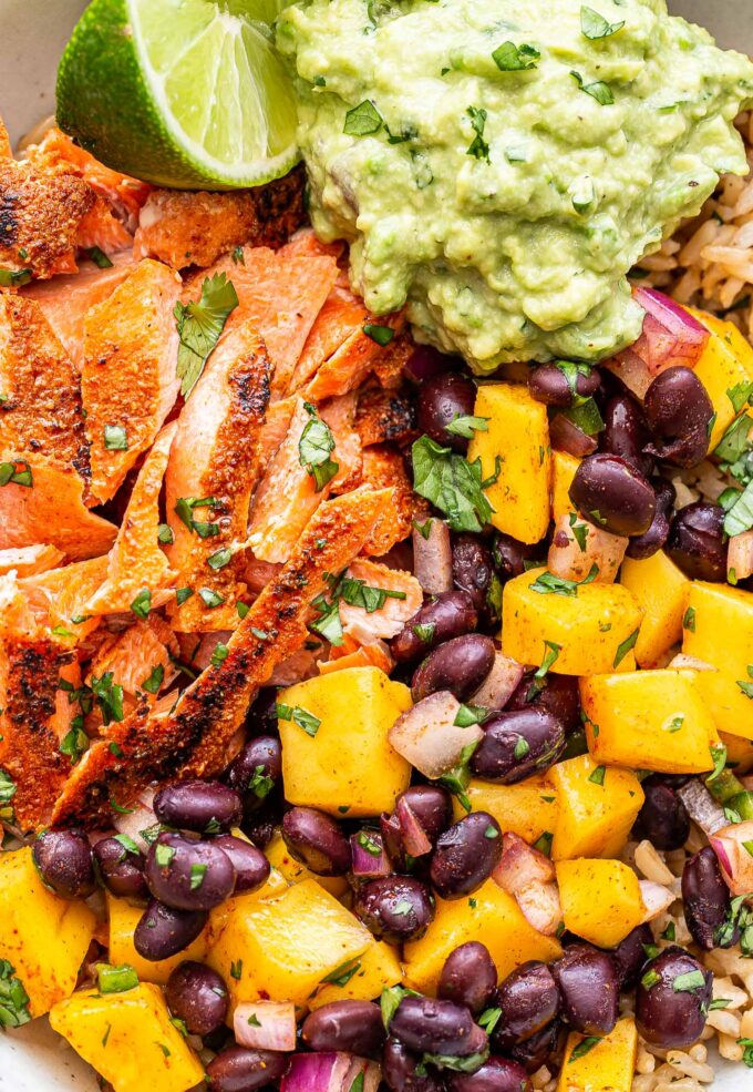 Closeup photo of Southwest Salmon Rice Bowls with mango black bean salsa and guacamole.
