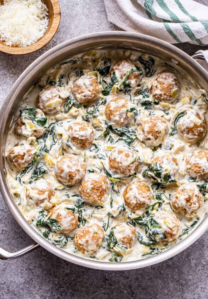 turkey meatballs in a creamy spinach artichoke dip sauce in a metal skillet.