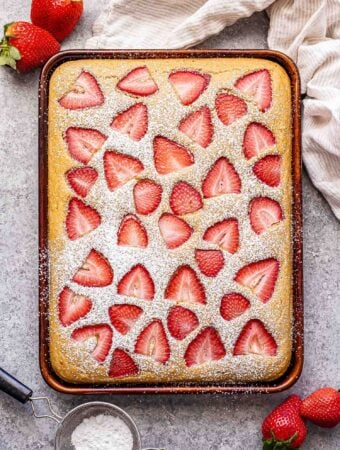 strawberry sheet pan pancakes topped with powdered sugar and strawberries next to the pan.