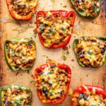 taco stuffed red and green bell peppers topped with melted cheese on a sheet pan.