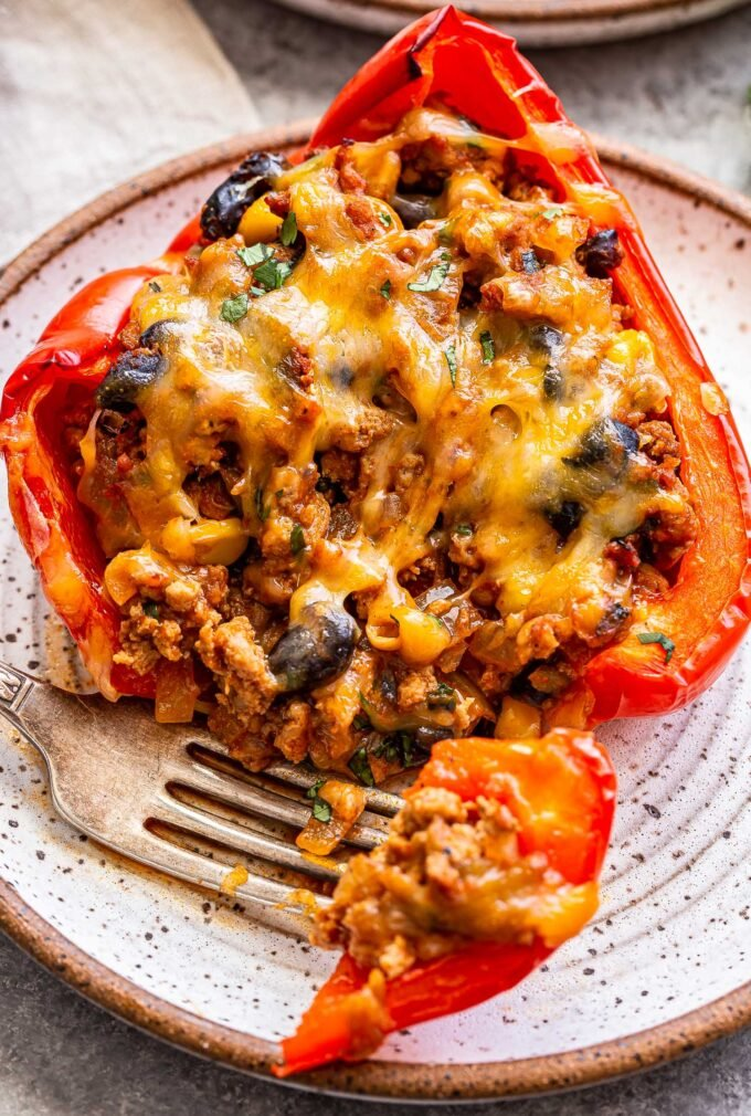 A taco stuffed pepper on a white plate with a fork holding a piece of it.