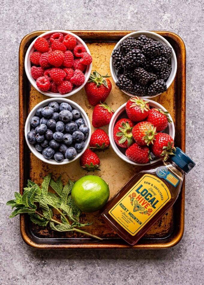 Ingredients used to make Berry Fruit Salad on a sheet pan.