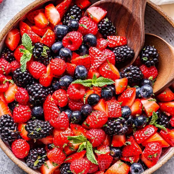 Berry Fruit Salad in white bowl with wooden spoons.