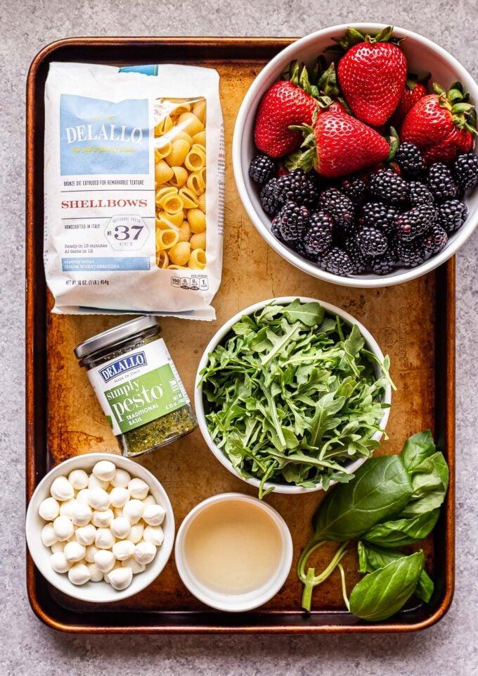 Ingredients used to make Berry Pesto Pasta Salad on a sheet pan.