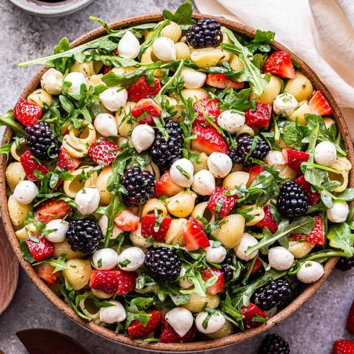 Berry Pesto Pasta Salad made with strawberries, blackberries, arugula and mozzarella balls in a white serving bowl. A small bowl of balsamic glaze behind the salad.