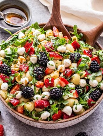 Berry Pesto Pasta Salad in a white bowl with wooden serving spoons. A small bowl of balsamic glaze behind the salad.