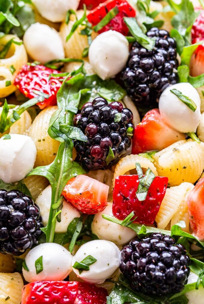 Closeup of Berry Pesto Pasta Salad with blackberries, arugula, strawberries and mozzarella balls