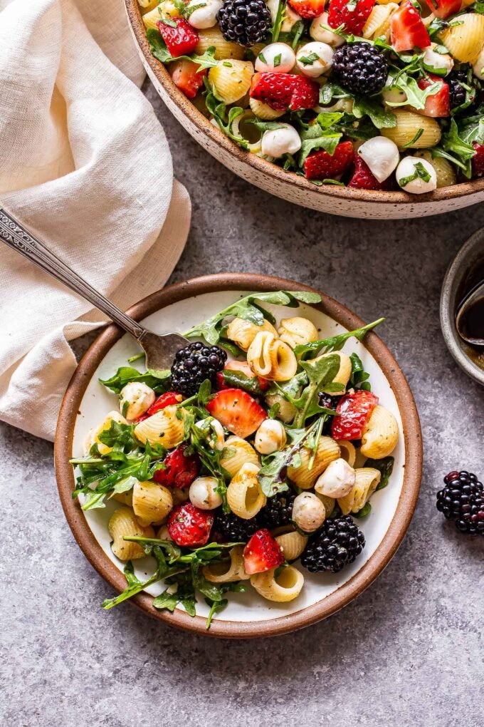 A serving of Berry Pesto Pasta Salad on a white plate with a fork and the serving bowl and a napkin behind it.
