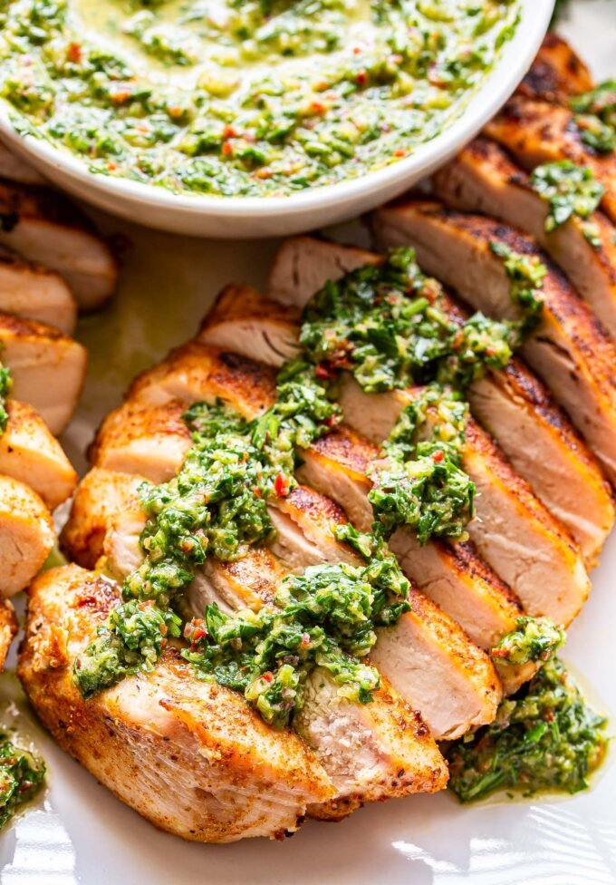 Sliced chicken breast topped with chimichurri on a white plate. A white bowl filled with chimichurri behind the chicken..