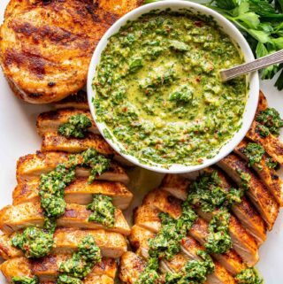 White plate with three chicken breasts on it and a bowl of chimichurri.