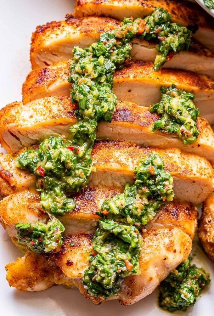 Sliced grilled chicken breast topped with chimichurri.
