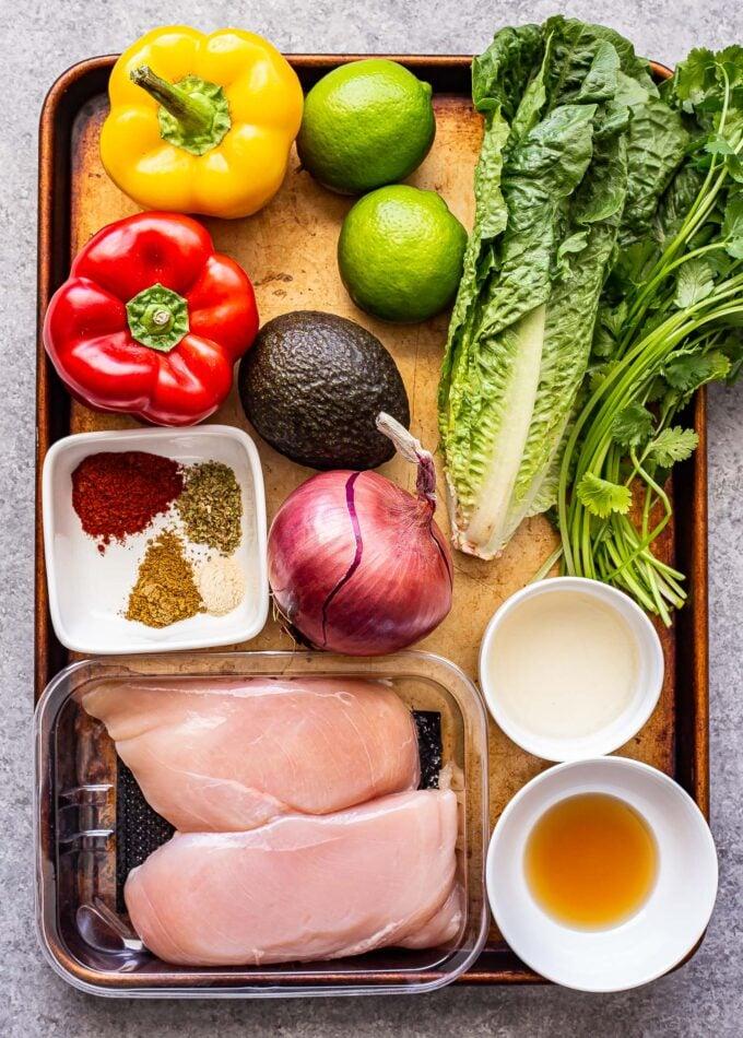ingredients used to make Grilled Chicken Fajita Salad on a sheet pan.