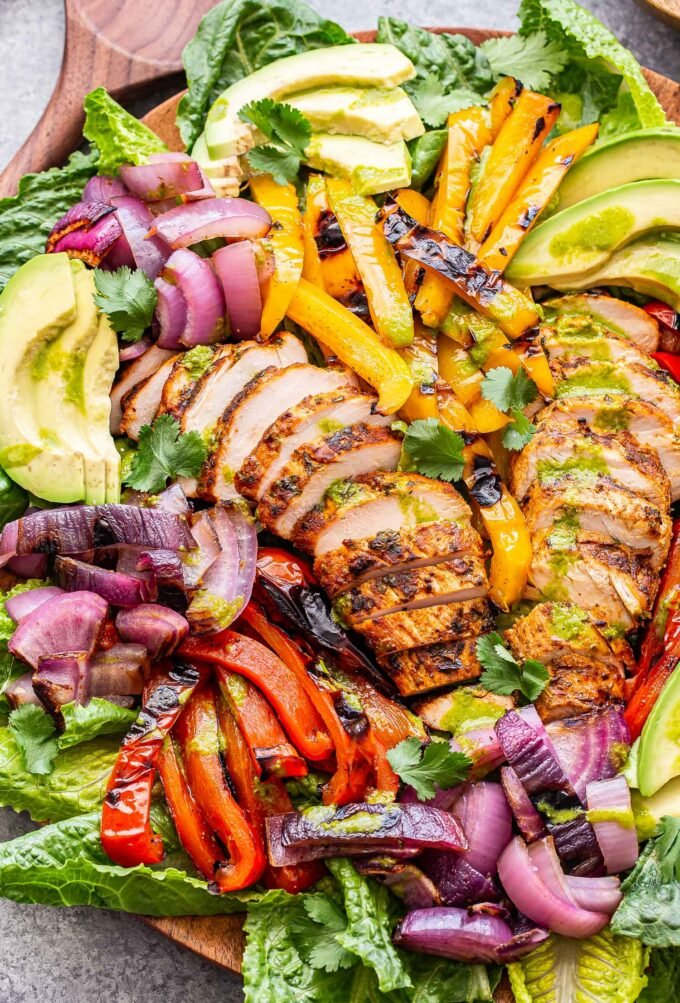 Grilled Chicken Fajita Salad made with grilled red and yellow peppers, red onion, avocado slices and drizzled with cilantro lime vinaigrette.