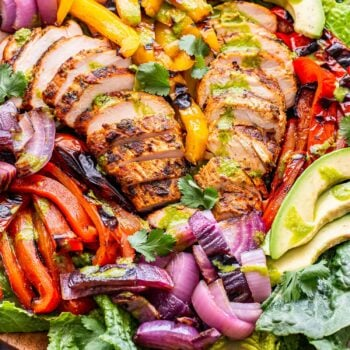 Grilled Chicken Fajita Salad on top of romaine with grilled peppers and onions and avocado slices.