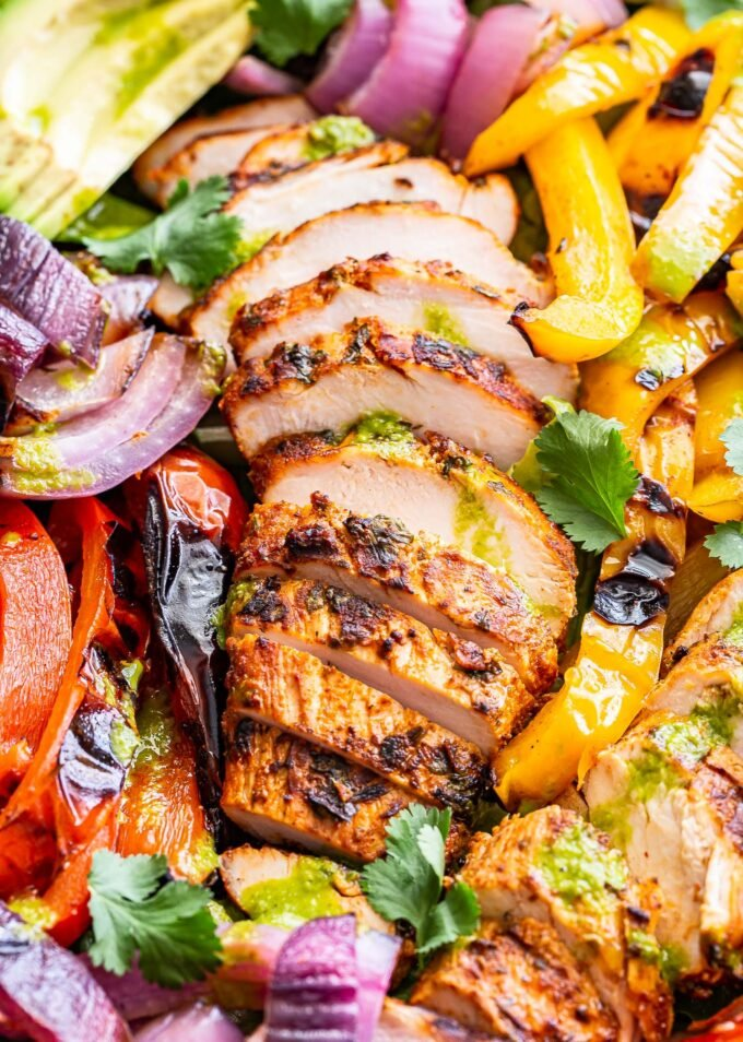 slices of grilled chicken on top of the Grilled Chicken Fajita Salad.