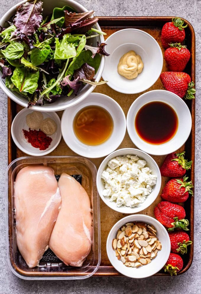 Grilled chicken salad with strawberries and goat cheese ingredients on a sheet pan