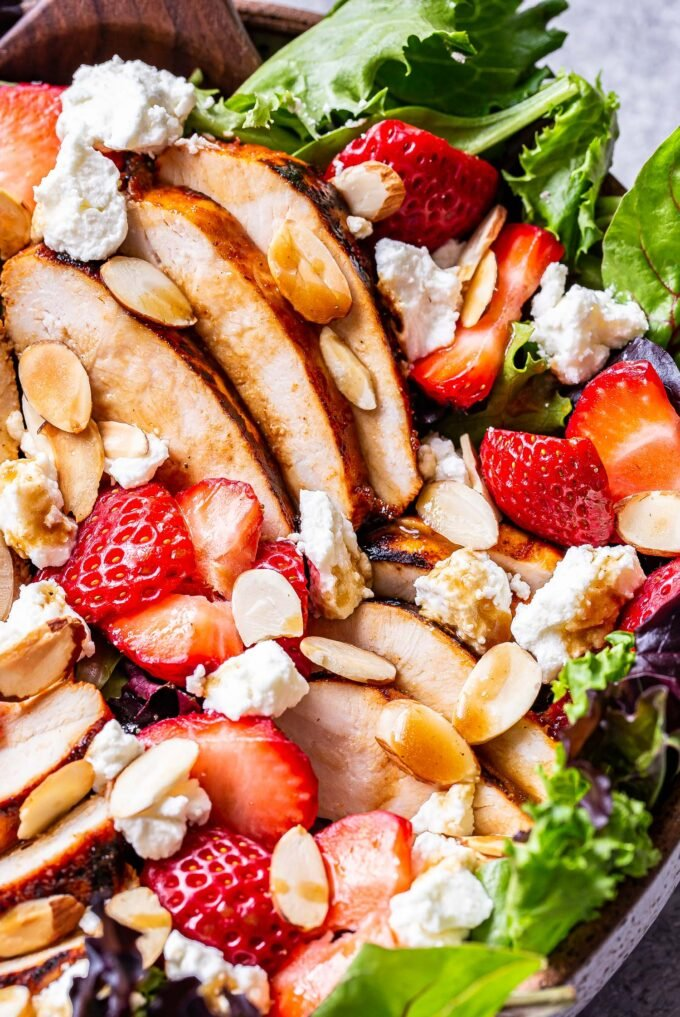Grilled Chicken Salad with Strawberries, Goat Cheese and sliced almonds on top of mixed greens.