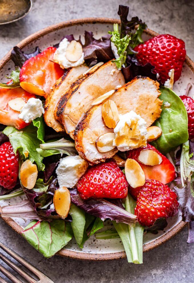 Grilled Chicken Salad with Strawberries and Goat Cheese on a round white plate.