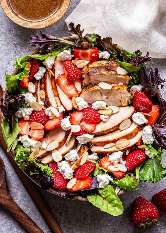 Grilled Chicken Salad with Strawberries and Goat Cheese in a bowl with wooden serving spoons to the left and a bowl of balsamic vinaigrette behind it.