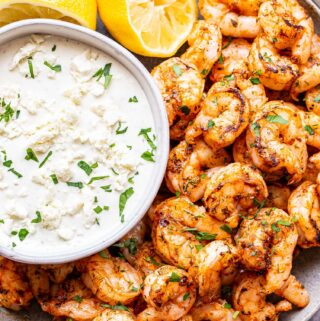 Spicy Shrimp with Feta Dip on a gray plate with two lemon halves.