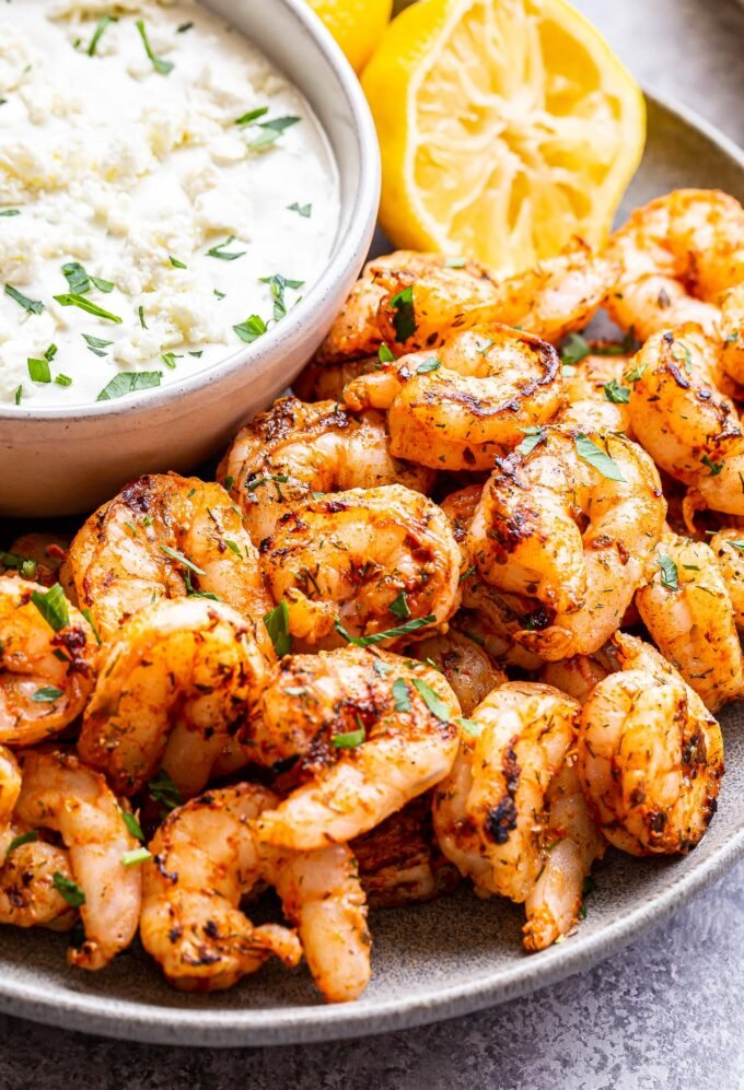 grilled spicy shrimp with a bowl of feta dip on a gray plate with a lemon half in the background.