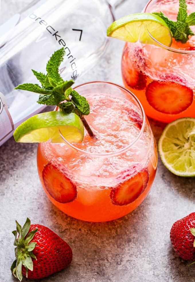Two Strawberry Lime Vodka Smash in glasses garnished with mint and lime slices.