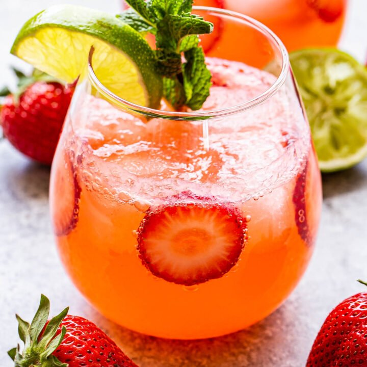 Strawberry Lime Vodka Smash garnished with mint, lime slice and strawberry slices.