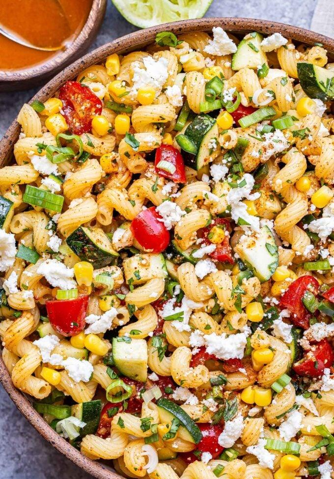 overhead photo of Tomato Corn Pasta Salad in a white serving bowl.