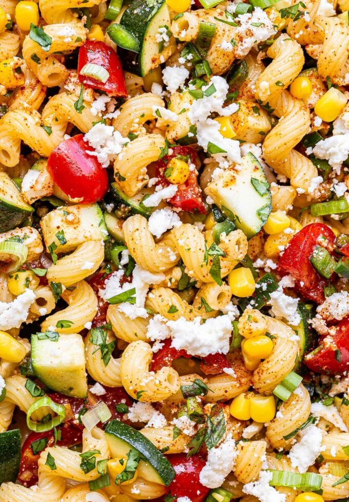 closeup of Tomato Corn Pasta Salad with zucchini and queso fresco.