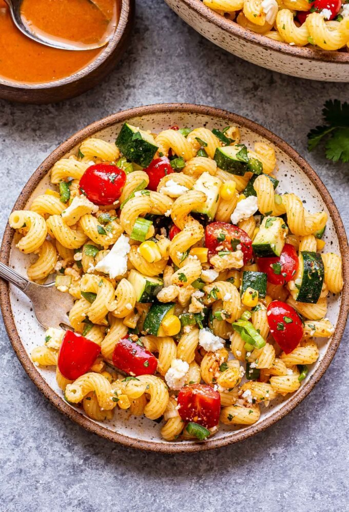 Tomato Corn Pasta Salad on a white plate with a fork