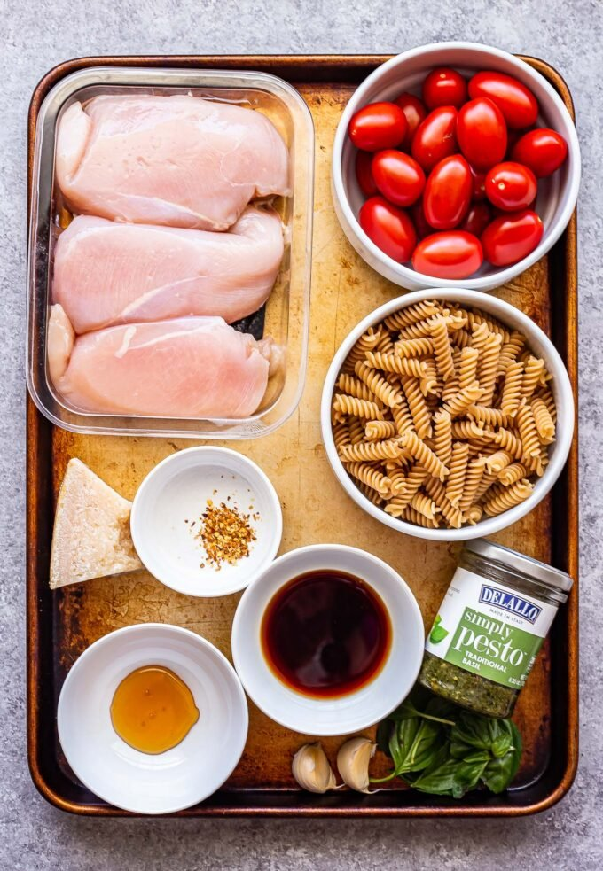 Ingredients used to make Tomato Basil Pasta with Balsamic Grilled Chicken on a sheet pan.