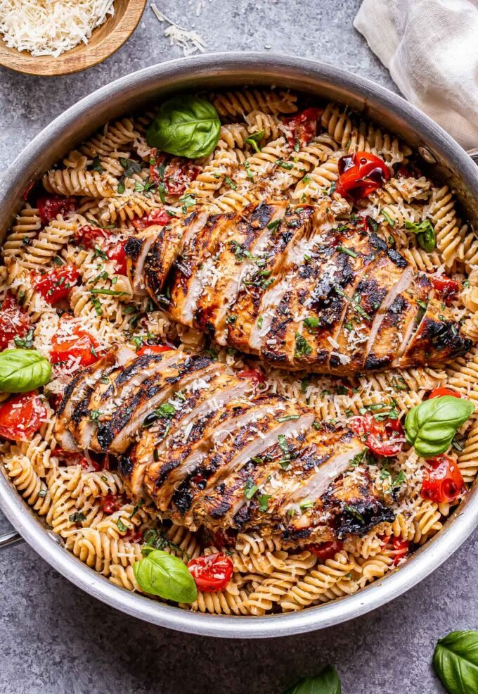 stainless steel pan filled with Tomato Basil Pasta with sliced Balsamic Grilled Chicken on top of it.