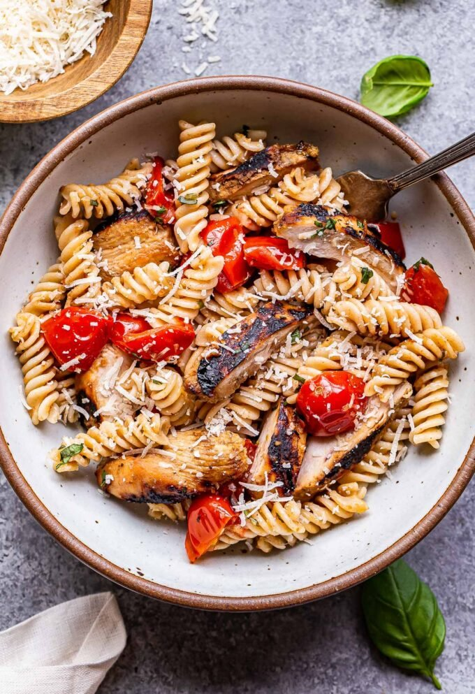 Tomato Basil Pasta with slices of Balsamic Grilled Chicken in a white bowl with a fork and bowl bowl of parmesan cheese behind it.