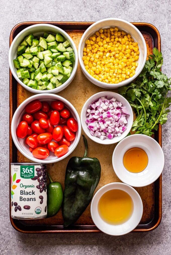 ingredients used to make black bean and corn salsa salad on a sheet pan.
