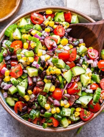 black bean and corn salsa salad in a white bowl with a wooden serving spoon.