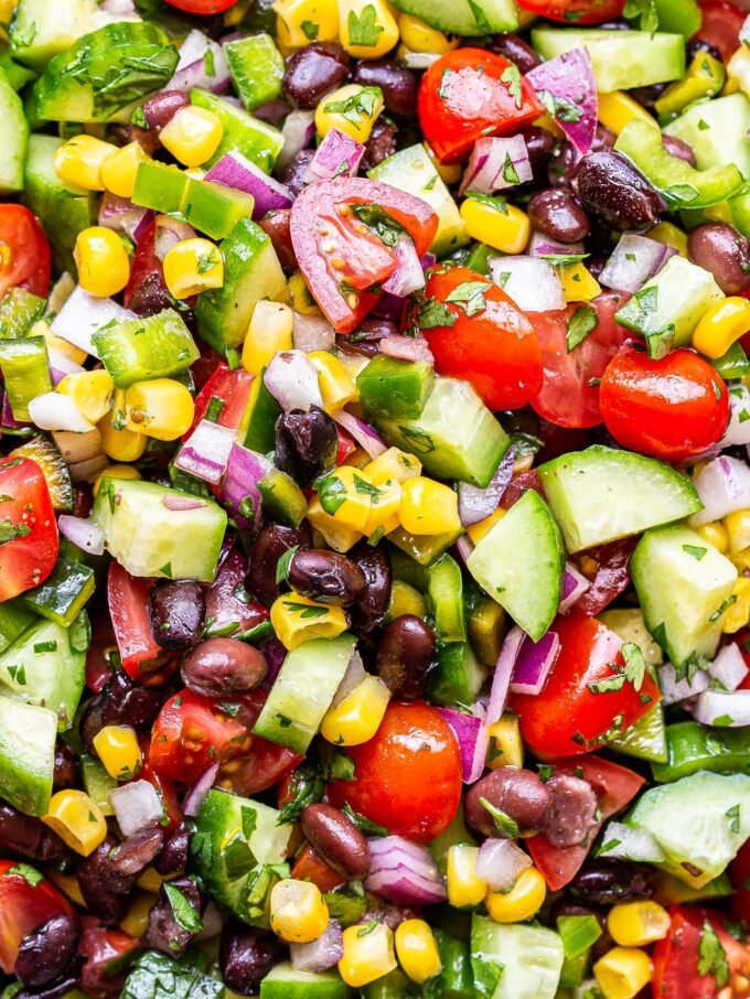 closeup photo of black bean and corn salsa salad with tomatoes, cucumbers, onion and cilantro.