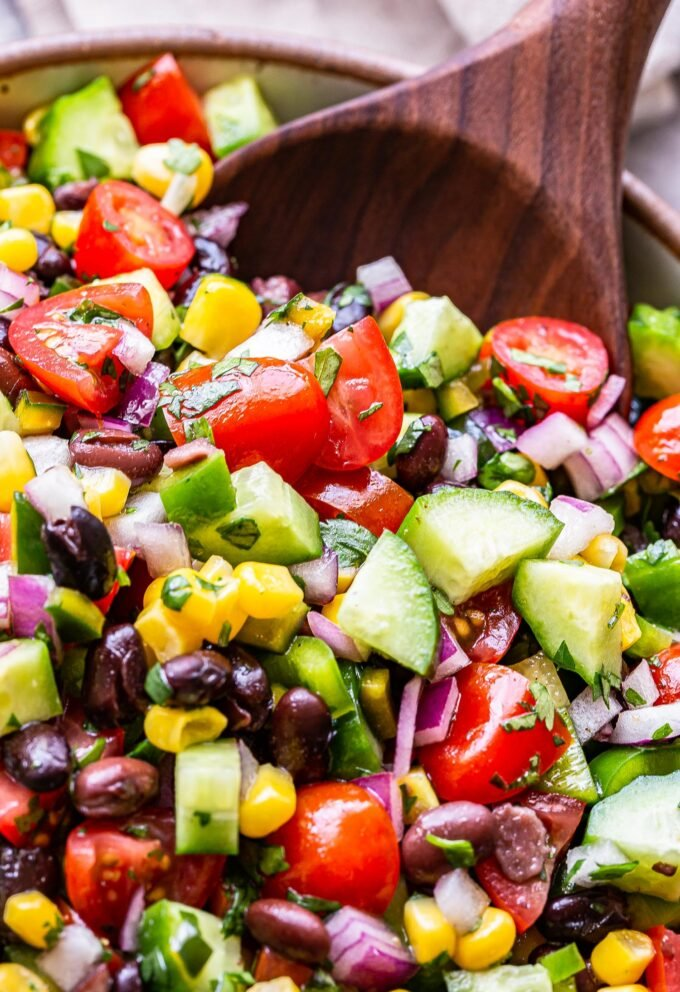 closeup of black bean and corn salsa salad with a wooden serving spoon in the bowl.