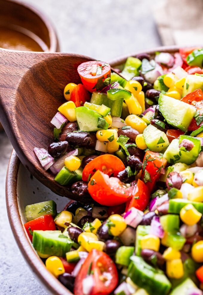wooden spoon scooping up black bean and corn salsa salad