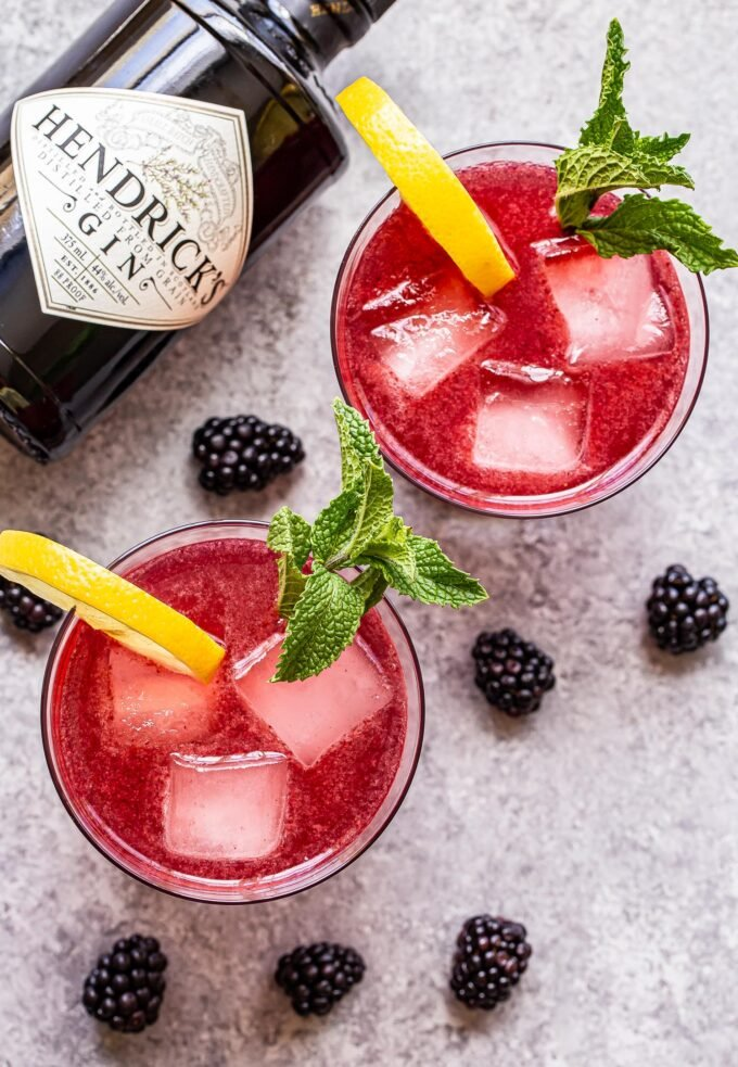 overhead photo of two blackberry gin fizz cocktails in glasses with lemon slices and mint sprigs for garnish. A bottle of gin is behind the glass.