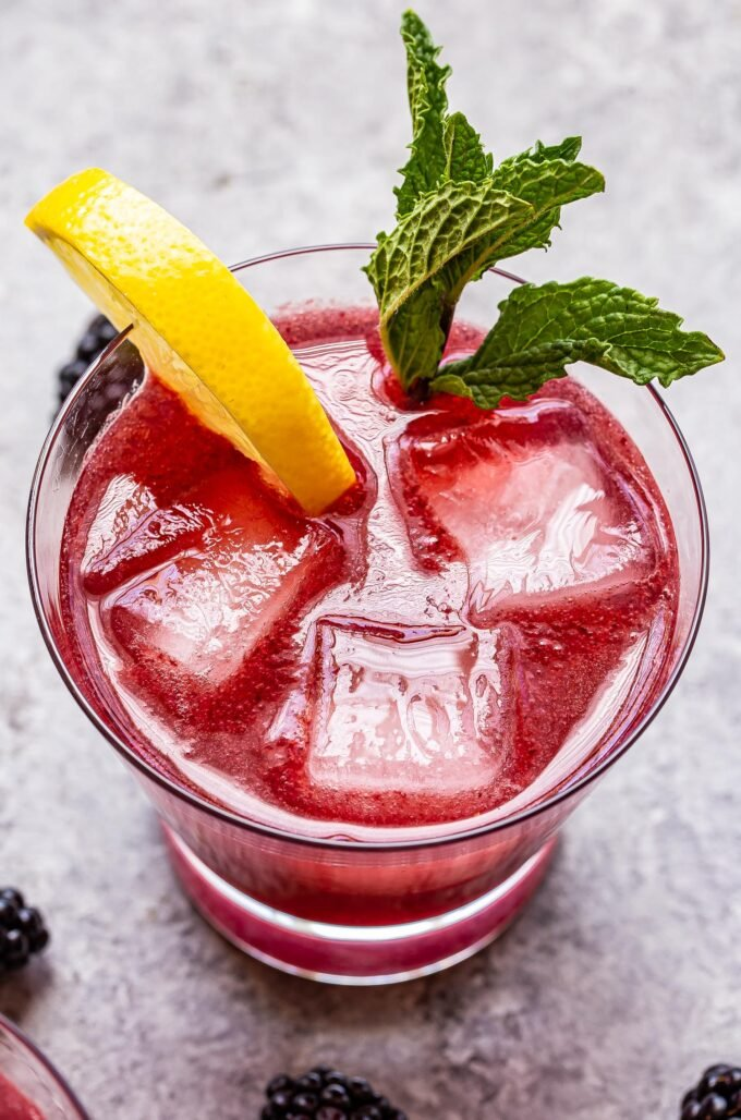 blackberry gin fizz cocktail in a glass with ice and a lemon slice and mint sprig for garnish.