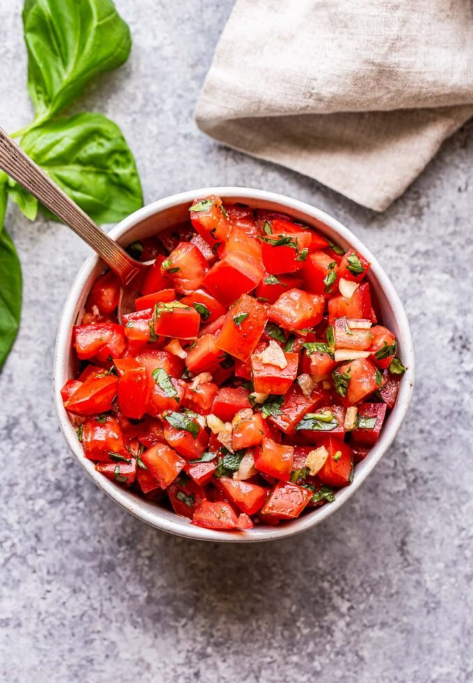 white bowl filled with tomato, basil, garlic topping grilled bruschetta chicken.