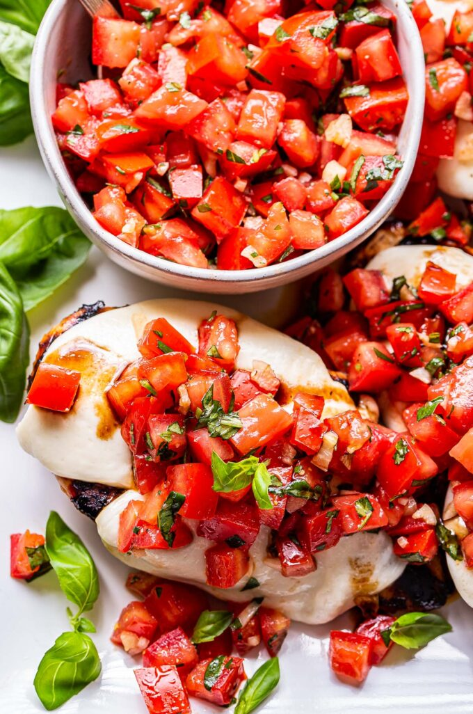 grilled chicken breast topped with melted mozzarella cheese and topped with a tomato basil topping. A bowl of the tomato basil topping is behind the chicken.