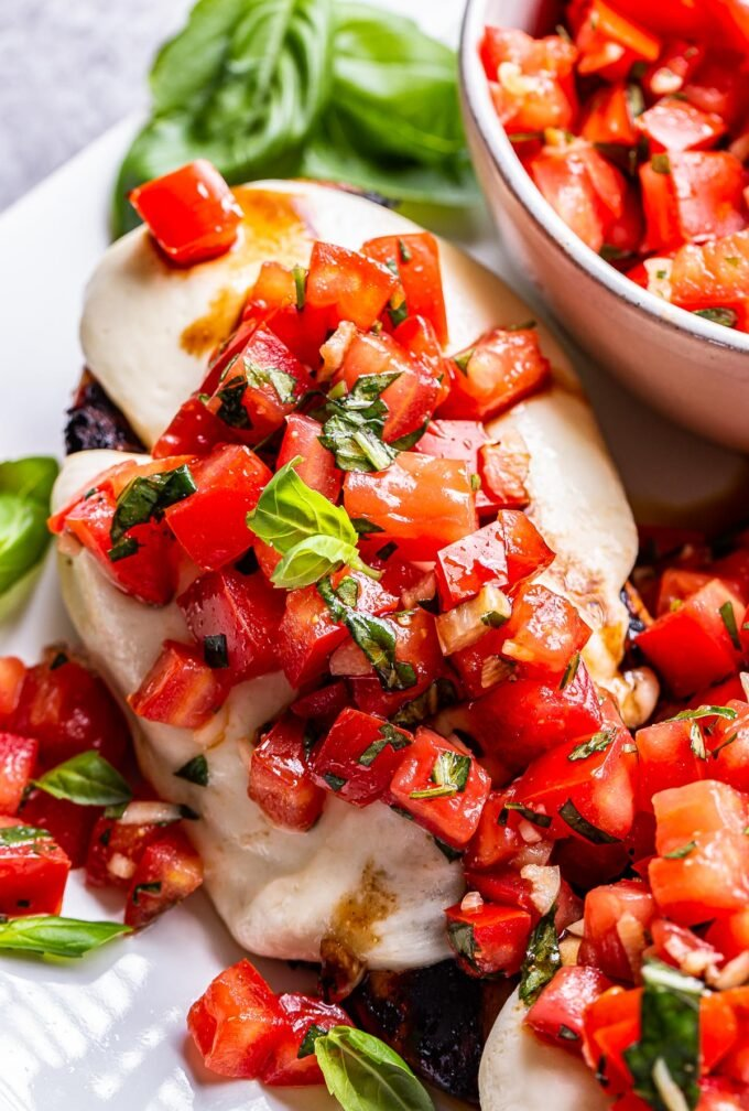 grilled chicken breast topped with melted mozzarella cheese and topped with a tomato basil topping.