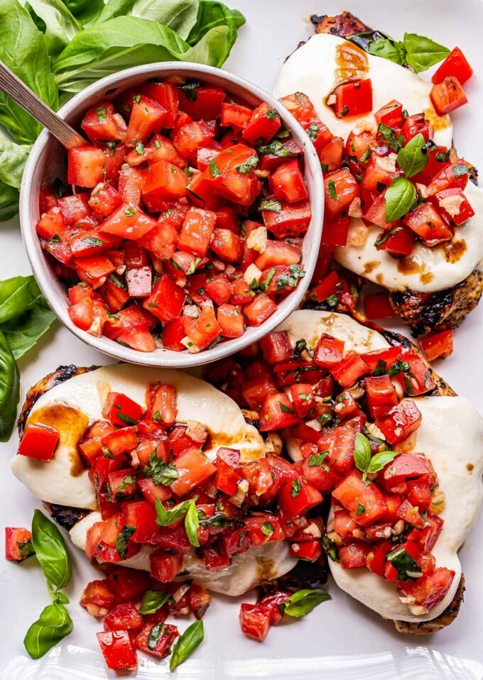 white serving plate with grilled chicken breasts topped with melted mozzarella and tomato basil topping. A bowl of the tomato basil topping on the plate as well.